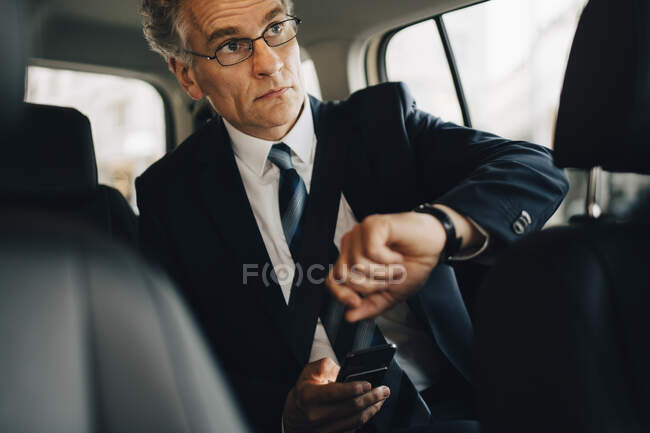 Businessman wearing wristwatch during business trip while sitting in taxi — Stock Photo