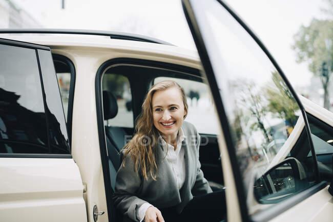 Sorridente imprenditrice uscire dal taxi durante il viaggio di lavoro — Foto stock