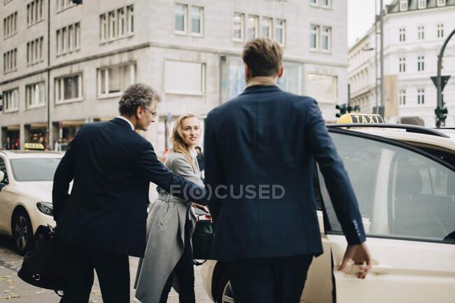 Ejecutivas masculinas y femeninas que viajan juntas para viajes de negocios - foto de stock