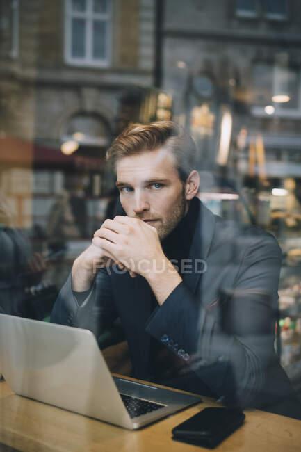 Портрет бізнесмена з ноутбуком сидить у кафе, яке видно через вікно скла. — стокове фото