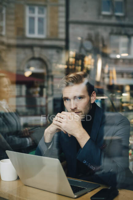 Portrait of businessman with laptop in cafe seen through glass window — Stock Photo