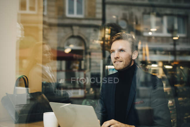 Smiling businessman with laptop looking away in cafe seen through glass window — Stock Photo