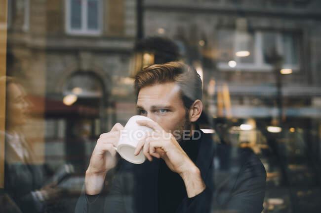 Uomo d'affari che beve caffè guardando lontano nel caffè visto attraverso la finestra di vetro — Foto stock