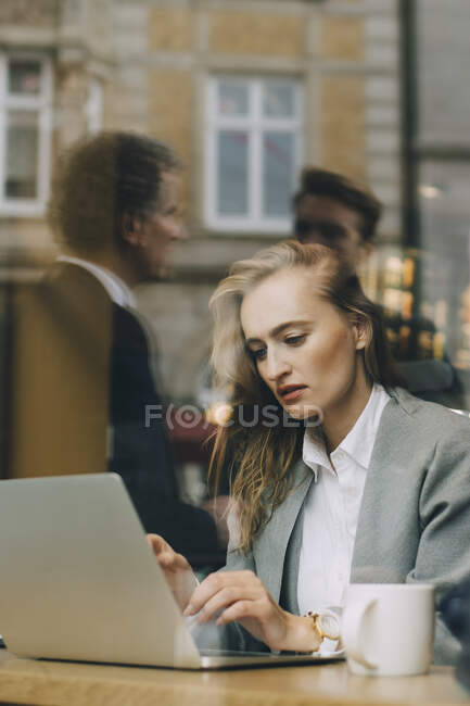 Безробітна жінка працює над ноутбуком у кафе, яке видно через вікно скла. — стокове фото