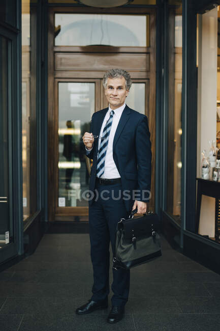 Portrait of businessman with bag standing by store in city — Stock Photo