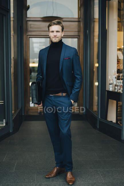Retrato de hombres de negocios con las manos en bolsillos de pie en la ciudad. - foto de stock