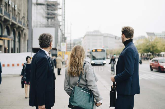 Geschäftsfrau mit männlichen Mitarbeitern in der Stadt — Stockfoto