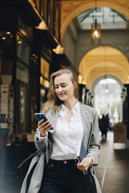 Smiling business woman using smart phone while standing in city - foto de stock