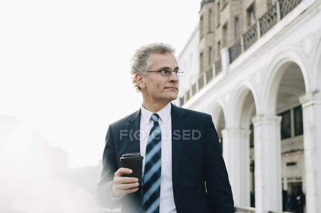 Homme d'affaires confiant avec tasse jetable regardant loin tout en se tenant en ville — Photo de stock