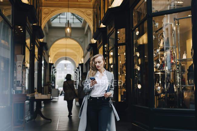 Contemplazione donna d'affari utilizzando smartphone mentre in piedi in città — Foto stock
