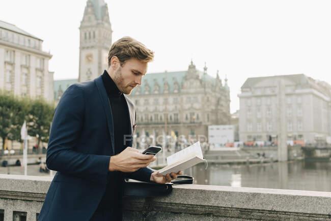 Бизнесмен со смартфоном смотрит на книгу, стоя в городе — стоковое фото