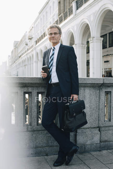 Portrait of confident businessman with disposable cup standing by retaining wall in city — Stock Photo