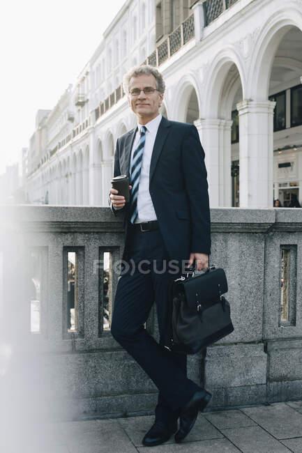 Retrato de hombre de negocios confiado con copa desechable manteniendo la pared en la ciudad. - foto de stock