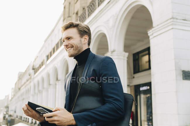 Смолящий бизнесмен со смартфоном смотрит в сторону, стоя против застройки в городе — стоковое фото