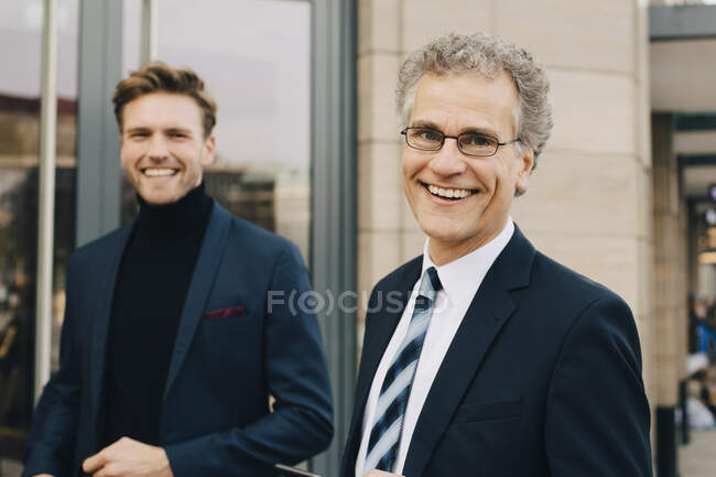 Portrait d'un homme entrepreneur heureux avec un collègue debout en ville — Photo de stock