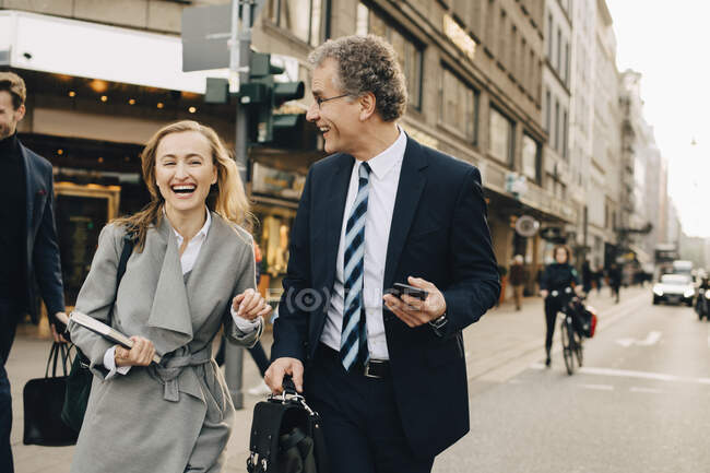 Happy female entrepreneur with male colleague crossing road in city — Stock Photo