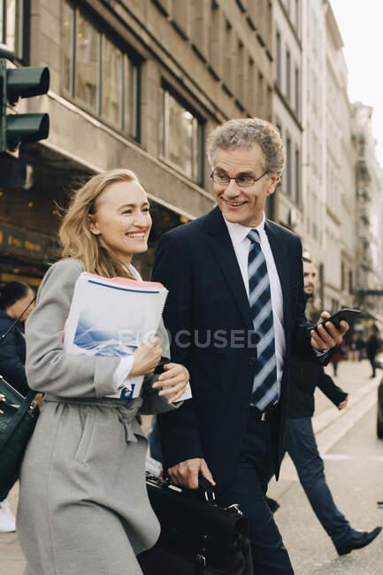 Femme entrepreneure souriante avec un collègue homme traversant la route en ville — Photo de stock