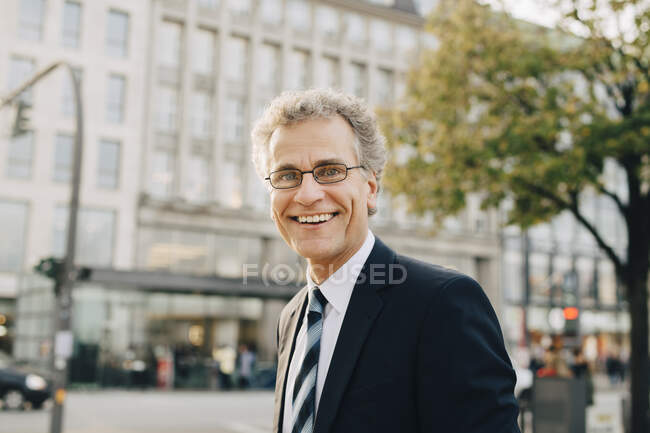 Portrait d'un homme d'affaires souriant portant un costume alors qu'il se tenait en ville — Photo de stock