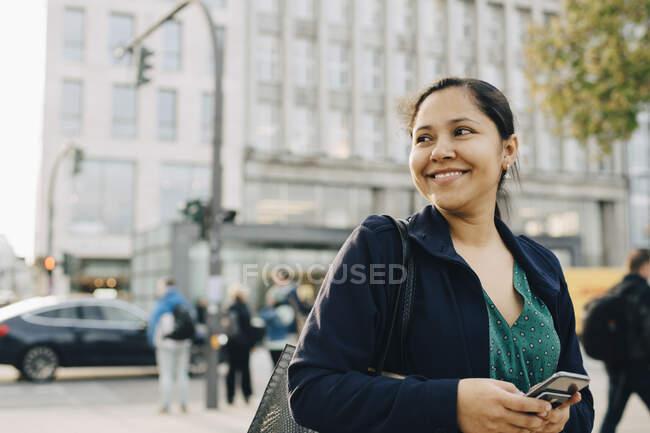 Sonriente empresaria con teléfono en la ciudad - foto de stock