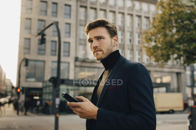 Непочтительный бизнесмен со смартфоном смотрит в сторону, стоя против застройки в городе — стоковое фото