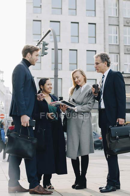 Collaboratori d'affari con libro discutere mentre in piedi in città — Foto stock