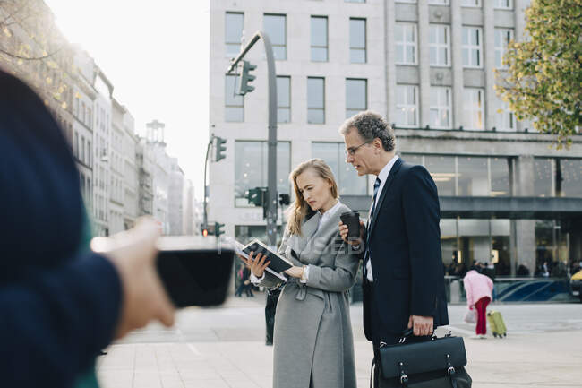 Business colleagues looking in book while standing in city — Stock Photo