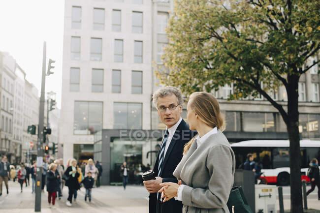 Mulher homem de negócios conversando com colegas de trabalho na cidade — Fotografia de Stock