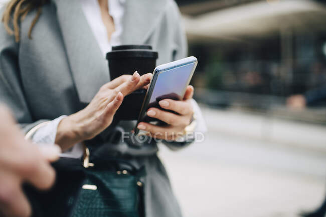 Midsection of business woman using phone in city - foto de stock