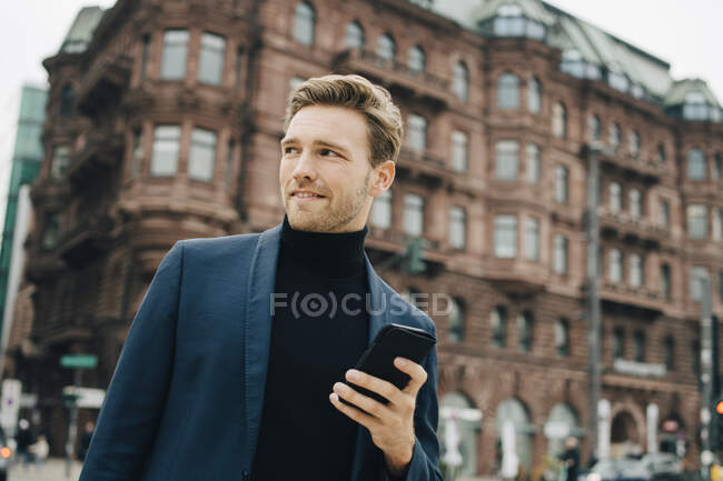 Confident businessman with smart phone looking away while standing against building in city — Stock Photo