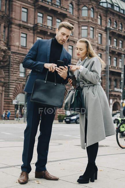 Uomo d'affari e donna d'affari utilizzando il telefono mentre in piedi in città — Foto stock