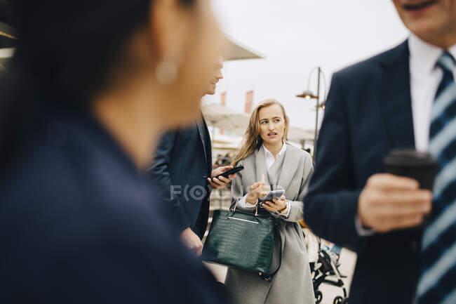 Contempler entrepreneur parler à un collègue masculin dans la ville — Photo de stock