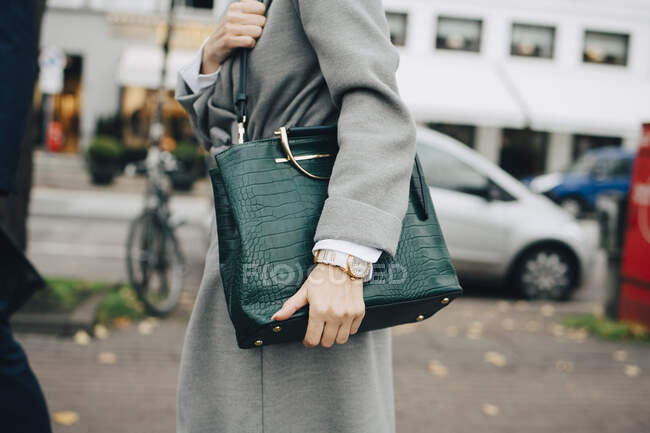 Midsection of business woman with handbag standing in city - foto de stock