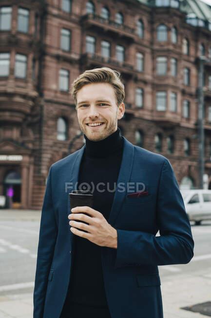 Портрет бизнесмена с одноразовой чашкой, выступающего против застройки в городе — стоковое фото