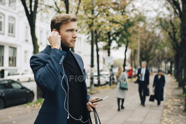 Empresarios que miran hacia otro lado mientras tienen auriculares en la ciudad - foto de stock
