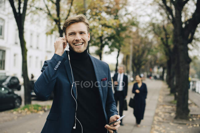 Smiling business man looking away while holding in-ear headphones in city. - foto de stock