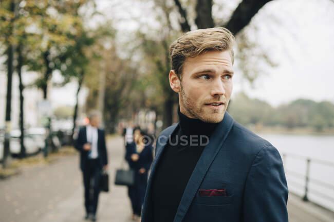 Contemplazione uomo d'affari guardando altrove mentre in piedi in città — Foto stock
