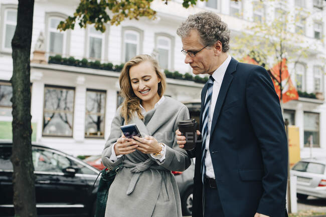 Smiling businesswoman showing smart phone to male coworker in city — Stock Photo