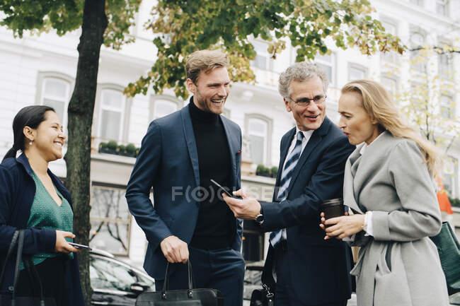 Lächelnder Unternehmer zeigt Kollegin Handy, während er bei Kollegen in der Stadt steht — Stockfoto