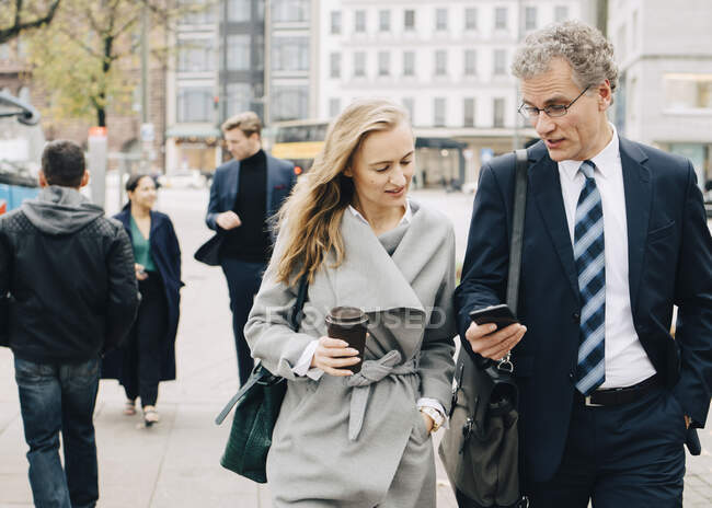 Businessman showing smart phone to female coworker while walking in city — Stock Photo