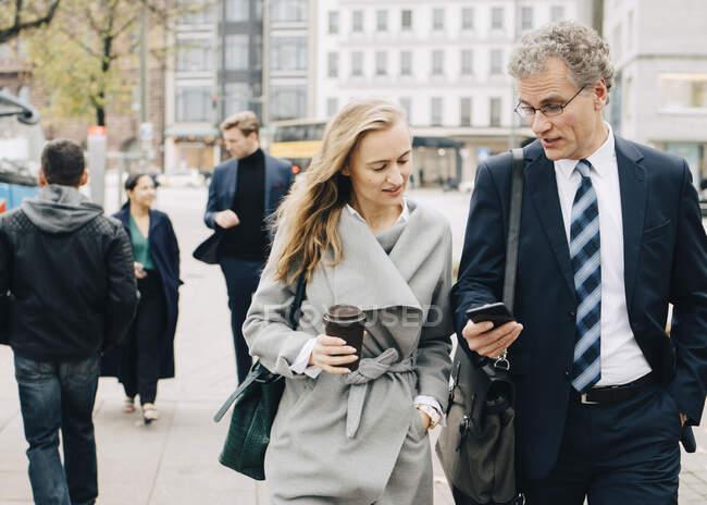 Geschäftsmann zeigt Mitarbeiterin beim Stadtbummel Smartphone — Stockfoto