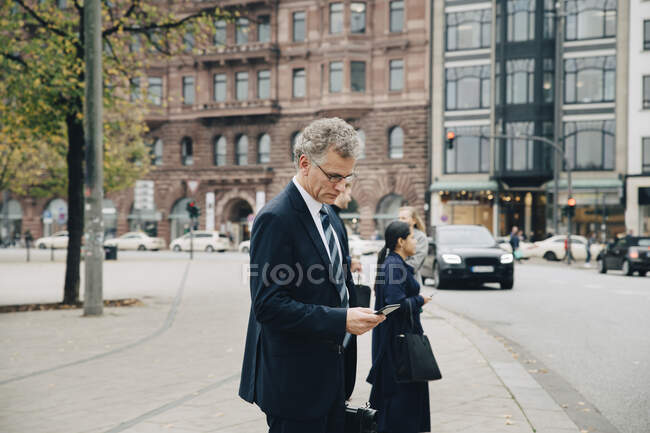 Side view of mature businessman using smart phone while standing in city — Stock Photo