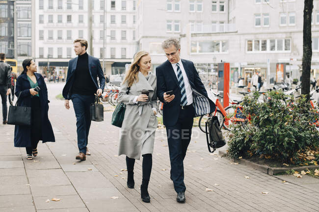 Businessman showing smart phone to female colleague while walking in city — Stock Photo