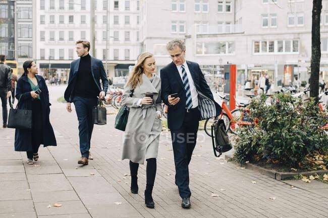 Homme d'affaires montrant le téléphone intelligent à une collègue en marchant dans la ville — Photo de stock