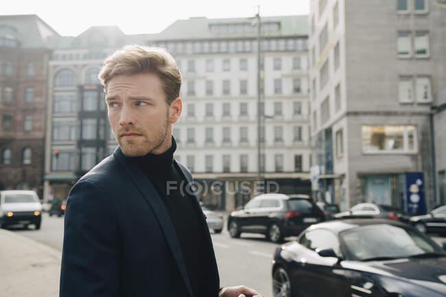 Предприниматель-мужчина смотрит в сторону, выступая против застройки в городе — стоковое фото