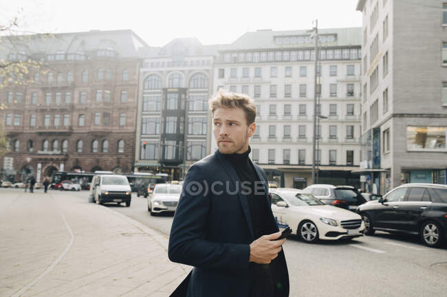 Contemplating entrepreneur with phone looking away while standing against building in city — Stock Photo