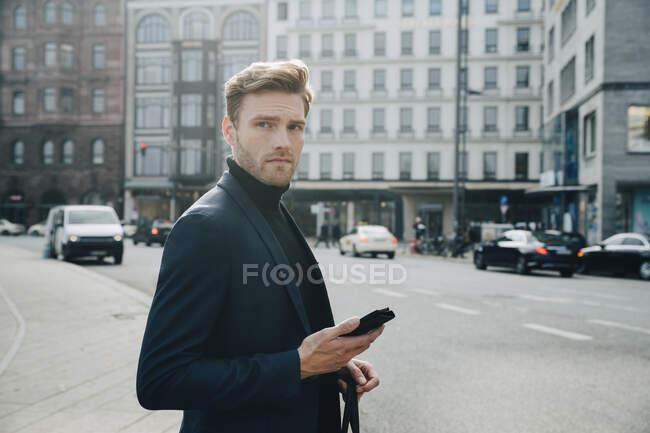 Вид сбоку на предпринимателя с телефоном, выступающего против застройки в городе — стоковое фото