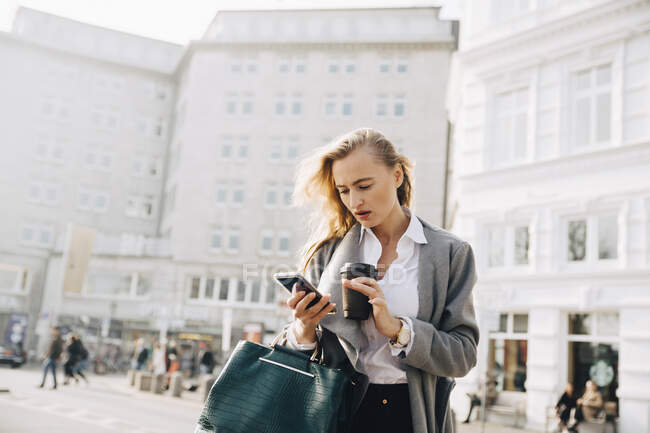 Worried entrepreneur using mobile phone while standing in city — Stock Photo
