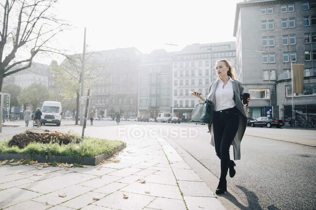 Largometraje completo de empresaria con teléfono inteligente caminando por la ciudad. - foto de stock