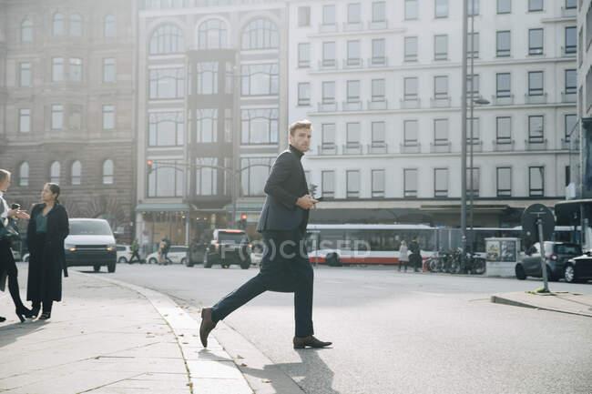 Vista lateral del empresario que camina por la carretera contra la construcción en la ciudad - foto de stock