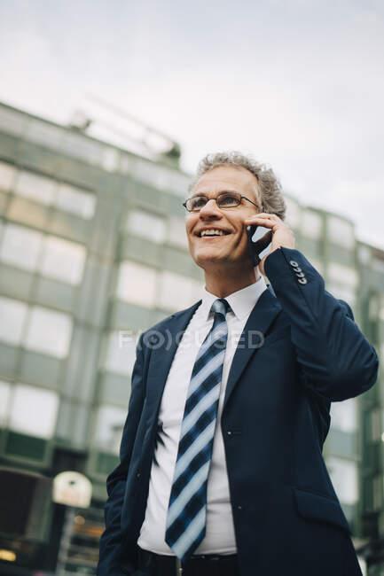 Vista a basso angolo di un uomo d'affari sorridente che parla attraverso lo smart phone mentre si trova in città — Foto stock